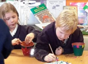 Children painting their plant pots