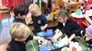 Children creating snow by using baking powder and shaving cream